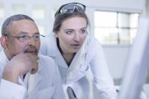 Two laboratory workers looking at computer screen — Stock Photo