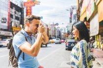 Молодой мужчина фотографирует девушку на улице, Бангкок, Таиланд — стоковое фото