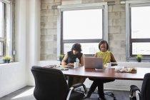Dos mujeres en la sala de reuniones usando el ordenador portátil y escribiendo en el cuaderno - foto de stock