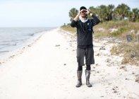 Vista frontal del hombre mirando a través de binoculares, al estar de pie en la playa - foto de stock