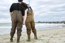 Jovem casal na pesca waders na praia — Fotografia de Stock