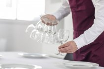 Waiter laying table in restaurant, mid section — Stock Photo