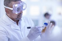 Laboratory worker writing details on test tube — Stock Photo
