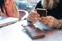 Mature hipster man using smartphone at sidewalk cafe, close up of tattooed hand — Stock Photo