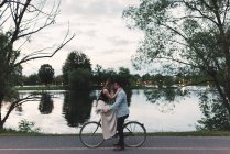 Romantic young couple on bicycle face to face by lake at dusk — Stock Photo