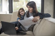 Девочка смотрит, как мама работает за ноутбуком на диване — стоковое фото