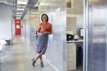Portrait of businesswoman standing in office corridor — Stock Photo
