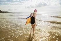 Молодая женщина с доской для серфинга в море — стоковое фото