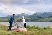 Пара в сельской местности, поставив палатку, Хини, штат Колорадо, Соединенные Штаты Америки — стоковое фото