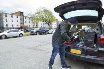 Jeune homme emballant canne à pêche dans le coffre de voiture — Photo de stock