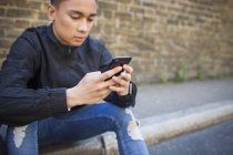 Молодой человек с помощью смартфона сидит на тротуаре — стоковое фото
