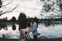 Romantic young couple on bicycle gazing at each other by lake at dusk — Stock Photo