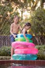 Young girl and boy having fun with inflatable rings at outdoor swimming pool — Stock Photo