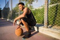 Jeune homme sur accroupi avec ballon de basket — Photo de stock