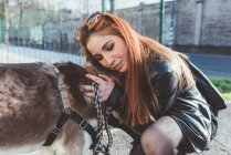 Red haired woman hugging dog — Stock Photo