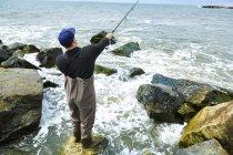 Jovem de pé na pesca do mar de rocha — Fotografia de Stock