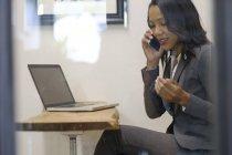 Зайнята жінка сидить в офісі за допомогою смартфона, ноутбука на столі. — стокове фото