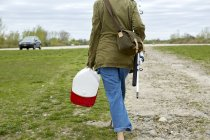 Young woman walking with fishing rod and tackle box — Stock Photo