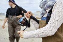 Femme en échassiers enroulement bobine de pêche sur la plage — Photo de stock