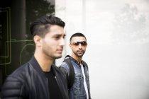 Двое друзей-мужчин идут по улице — стоковое фото