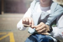 Mid section view of Young man rolling cigarette sitting outdoors — Stock Photo