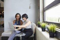 Dos empresarias que trabajan con el ordenador portátil en la oficina moderna - foto de stock