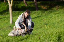 Man playing with dog on grass in park — Stock Photo