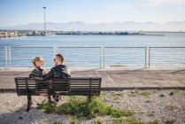 Rear view of couple sitting on bench, Cagliari, Sardinia, Italy, Europe — Stock Photo