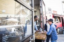 Customer paying vendors in food truck — Stock Photo