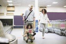 Père, transportant la fille dans les bagages à l'aéroport de chariot — Photo de stock