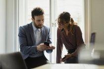 Двое коллег в офисе смотрят на смартфон — стоковое фото