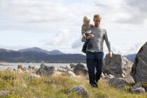 Man carrying son by fjord, Aure, More og Romsdal, Norway — Stock Photo