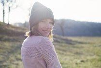 Портрет женщины в солнечном поле, оглядывающейся через плечо — стоковое фото
