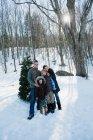 Портрет сім'ї стоячи в засніжений ліс — стокове фото