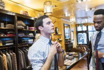 Customer fastening tie in tailor shop — Stock Photo