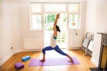 Vista laterale della donna con le braccia sollevate in posizione yoga — Foto stock