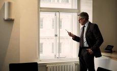 Hombre de negocios maduro en mensajes de texto de oficina en el teléfono inteligente - foto de stock