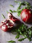 Close up of Pomegranate on grey surface, rocket lettuce — Stock Photo