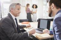 Бізнесменів в офісі говорити і використання ноутбука — стокове фото
