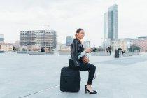 Portrait de femme d'affaires assis sur la valise en plein air — Photo de stock