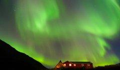 Landscape with log cabin and aurora borealis at night, Narsaq, Vestgronland, South Greenland — Stock Photo