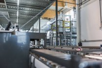 Factory interior, with conveyor belt in foreground — Stock Photo