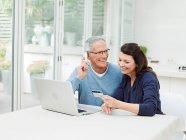 Casal maturo usando laptop e cartão de crédito — Fotografia de Stock