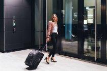 Женщина по строительству тянет колесные чемоданы — стоковое фото