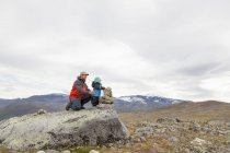 Male hiker with son building cairn in mountain landscape, Jotunheimen National Park, Lom, Oppland, Norway — Stock Photo
