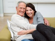 Coppia matura che si abbraccia sul divano in soggiorno — Foto stock