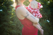 Frau trägt Baby im Arm im Garten — Stockfoto