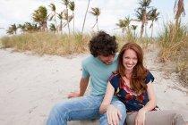 Portrait de jeune couple assis sur la plage — Photo de stock