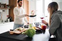 Couple cooking food, tossing vegetables in frying pan — Stock Photo