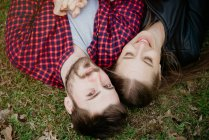 Overhead view of couple lying down on grass — Stock Photo